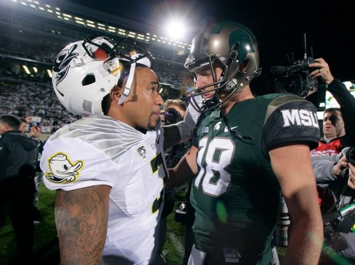 Oregon quarterback Vernon Adams Jr., left, and Michigan State quarterback Connor Cook (18) talk following an NCAA college football game, Saturday, Sept. 12, 2015, in East Lansing, Michigan.Michigan State won 31-28. (Al Goldis/AP)