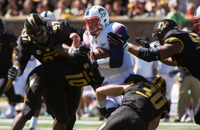 Connecticut quarterback Bryant Shirreffs, center, is gang tackled by Missouri's Rickey Hatley, right, Josh Augusta, left, Michael Scherer (30) and Kentrell Brothers (10) during the fourth quarter of an NCAA college football game Saturday, Sept. 19, 2015, in Columbia, Missouri. (L.G. Patterson/AP)