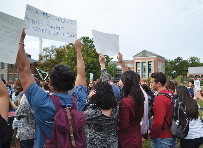 Attendees of the Students for Bernie Sanders hold up signs on the Student Union Mall on Sept. 22, 2015. (Amar Batra/The Daily Campus)
