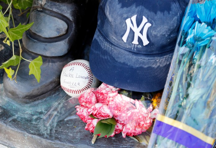 A ball placed by Aaron Bertone, 9, of Clifton, N.J., is seen at the feet of a statue of former New York Yankees hall of fame catcher Yogi Berra outside of the Yogi Berra Museum, Wednesday, Sept. 23, 2015, in Little Falls, N.J. Berra died Tuesday at the age of 90. (Julio Cortez/AP)