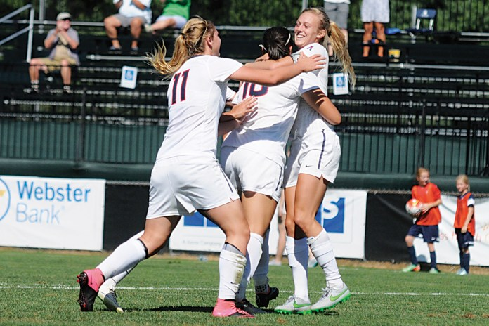 Members of the UConn women's soccer team celebrate with forward Rachel Hill (far right) after her late game winner against Harvard on Sunday, Sept. 6, 2015. (Amar Batra/The Daily Campus)