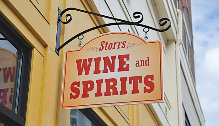In this photo, the Storrs Wine and Spirits sign hands above the storefront in Storrs Center.On Sept. 11, several students from the University of Connecticut were arrested outside Storrs Wine and Spirits for providing alcohol to minors. (Amar Batra/The Daily Campus)