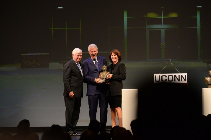 Former President Bill Clinton, center, accepts the Thomas J. Dodd Prize in International Justice and Human Rights from Helena Foulkes (right),acting chair, national advisory board of the Thomas J. Dodd Research Center and former Connecticut Sen. Chris Dodd (left) at the Jorgensen Center for the Performing Arts in Storrs, Connecticut on Thursday, Oct. 15, 2015. (Ashley Maher/The Daily Campus)