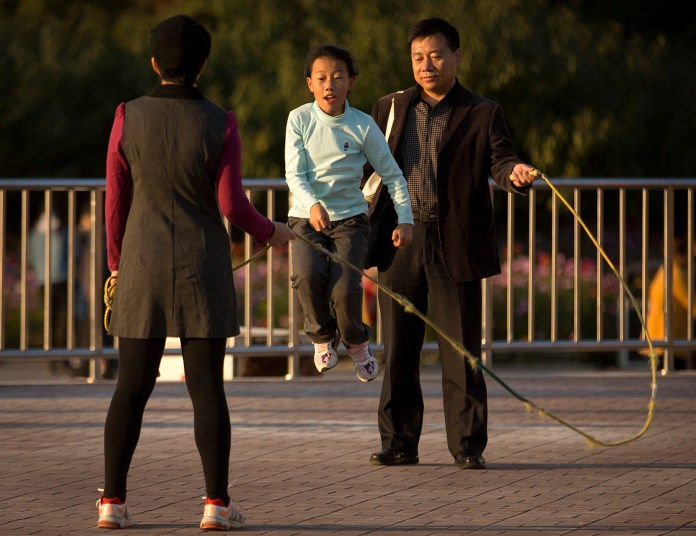 A man and woman twirl a jump rope for a girl at a park in Beijing, Saturday, Oct. 31, 2015. China's ruling Communist Party announced Thursday that the country will start allowing all couples to have two children, abolishing an unpopular policy that limited many urban couples to only one child. (Mark Schiefelbein/AP)