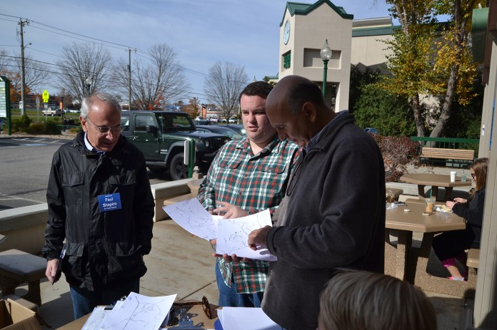 Town council member Paul Shapiro (left) and other members of Mansfield Democrats plan a campaign route in the Storrs Commons shopping area in Mansfield, Connecticut on Saturday, Oct. 31, 2015. Democrats campaigned door-to-door to raise awareness about their campaign. Election Day is Nov.3. (Amar Batra/The Daily Campus)