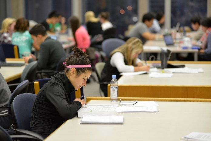 A student studies in the library. Reading days, or days during finals week that don't have exams, are often complained about by students because they're not placed efficiently. (Jason Jiang/Daily Campus)