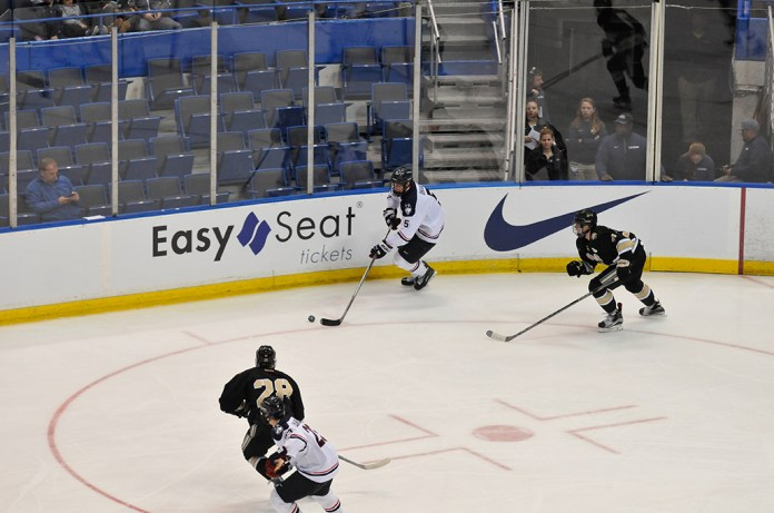 UConn sophomore defender David Drake (middle) handles the puck during the Huskies' game against Army at the XL Center in Hartford, Connecticut on Tuesday, Nov. 10, 2015. The team is currently riding a six-game losing streak. (Amar Batra/The Daily Campus)