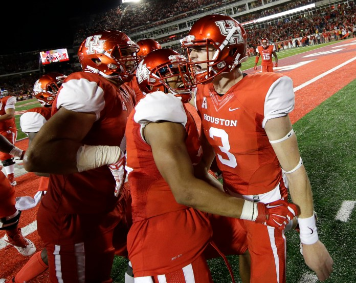 Houston quarterback Kyle Postma (3) celebrates with Chance Allen, center, and teammates after scoring a touchdown during the fourth quarter of an NCAA college football game against Memphis, Saturday, Nov. 14, 2015, in Houston. (David J. Phillip/AP)