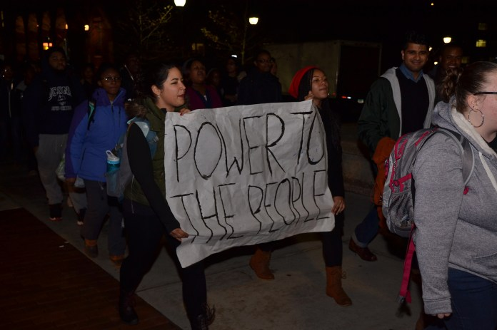 """Students walk during the """"March for Justice, Empowerment and Solidarity,"""" holding a sign that reads """"Power To The People"""" on Fairfield Way in Storrs, Connecticut on Thursday, Nov. 19, 2015. (Amar Batra/The Daily Campus)"""