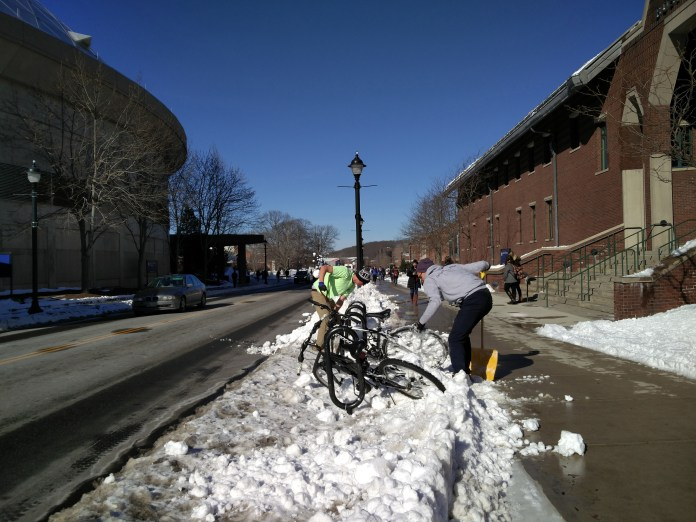 UConn students are seen shoveling snow on the UConn campus. There were over 200 student applications for snow shoveling work this semester, according to Facilities Operations and Building Services. (Jason Jiang/The Daily Campus)