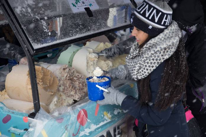 A student scoops ice cream during SUBOG's One Ton Sundae event outside the Student Union in Storrs, Connecticut on Friday, Feb. 6, 2016. (Jackson Haigis/The Daily Campus)