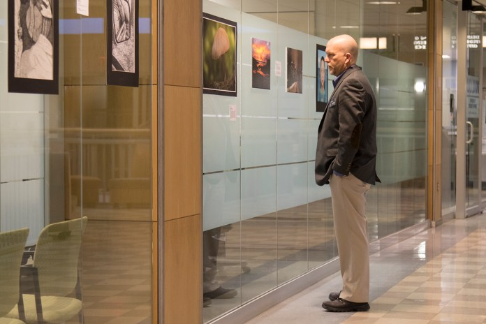 John Bau, a career consultant in UConn's School of Engineering,views artwork during a student art exhibition hosted by the Center for Career Development on the second floor of the Wilbur Cross Building on Wednesday, Feb. 10, 2016.(Jackson Mitchell/The Daily Campus)