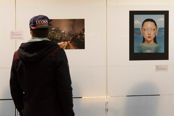 A student views artwork during a student art exhibition hosted by the Center for Career Development on the second floor of the Wilbur Cross Building on Wednesday, Feb. 10, 2016.(Jackson Mitchell/The Daily Campus)
