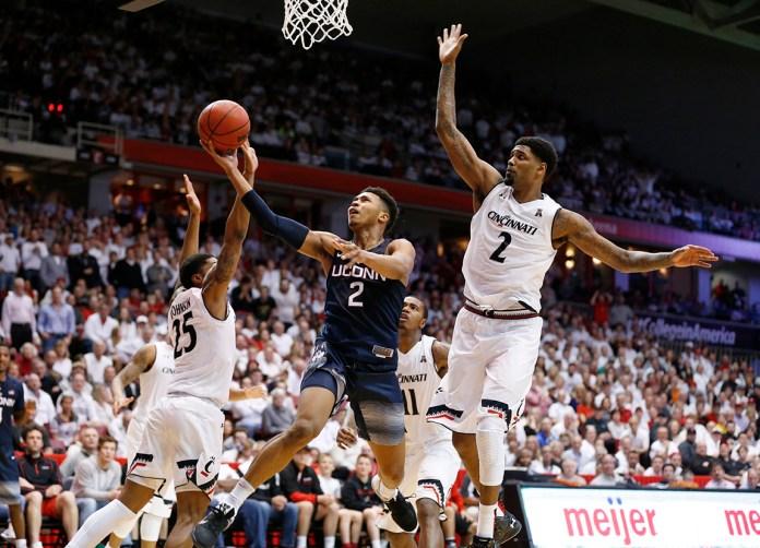 Connecticut guard Jalen Adams, center, shoots between Cincinnati's Kevin Johnson (25) and Octavius Ellis (2)during the second half of an NCAA college basketball game Saturday, Feb. 20, 2016, in Cincinnati. (AP Photo/Gary Landers)