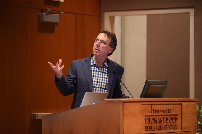 """Sports Illustrated writer Alexander Wolff gives a lecture on his book """"The Audacity of Hoop""""in the Konover Auditorium at the Dodd Center on Monday, March 22. (Zhelan Lang/The Daily Campus)"""