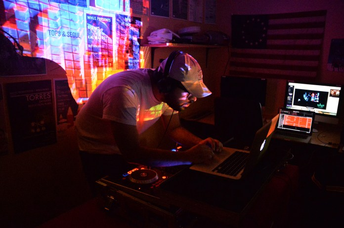 WHUS General Manager Santiago Pelaez browses his computer during the radio station's Livestream Mix Cypher event in the UConn Student Union on Friday, March 25, 2016. (Amar Batra/The Daily Campus)