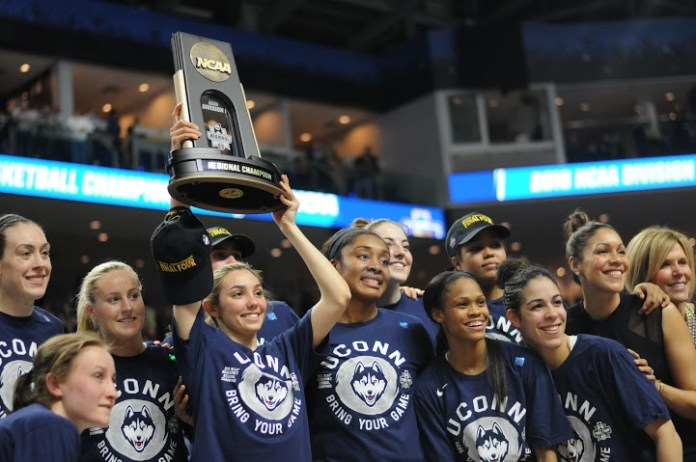 UConn senior Briana Pulido hoists the 2016 NCAA Bridgeport regional championship trophy on Monday, March 28 at Webster Bank Arena in Bridgeport, Connecticut. Morgan Tuck led the Huskies with 22 points en route to an 86-65 win over No. 2 seed Texas. (Bailey Wright/The Daily Campus)
