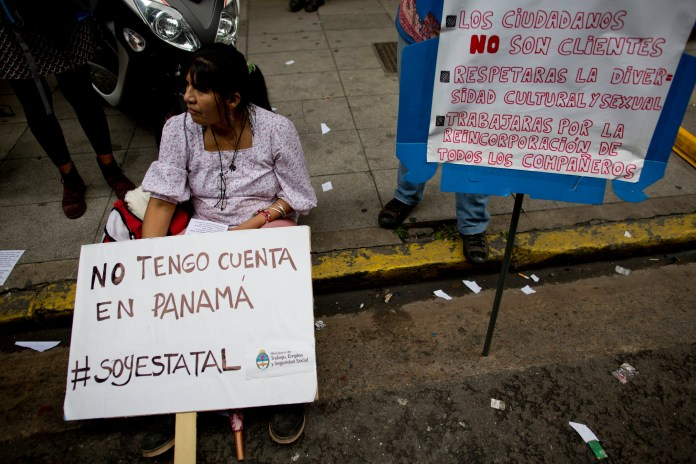 """A worker demonstrates outside the Labor Ministry with a sign that reads in Spanish """"I don't have an account inPanama,"""" in Buenos Aires, Argentina, Wednesday, April 6, 2016. Her sign is a jab at Argentina's President Mauricio Macri, whose family name was included in documents leaked from a panama law firm, coined the """"panama papers,"""" that lists his family in connection with a Bahamas-based offshore company. Ministry workers are on strike to demand the immediate reinstatement of dismissed workers. (AP Photo/Natacha Pisarenko)"""