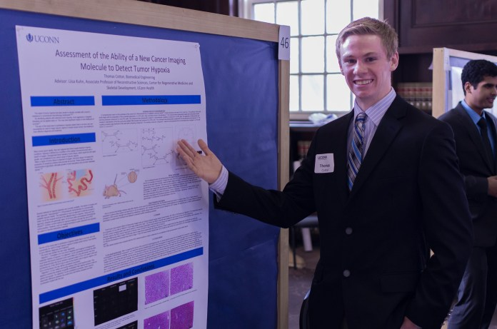 UConn biomedical engineering student Thomas Cotton presents his research results on a poster in the Wilbur Cross Building during Frontiers in Undergraduate Research, UConn's annual research poster exhibition, on Saturday, April 9, 2016. (/The Daily Campus)