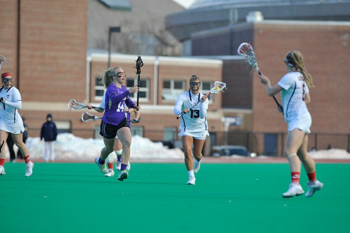 Carly Palmucci, #13, looks to make a pass during UConn's 12-10 victory over James Madison on Feb 21, 2015 at the Sherman Sports Complex. (Jason Jiang/The Daily Campus)