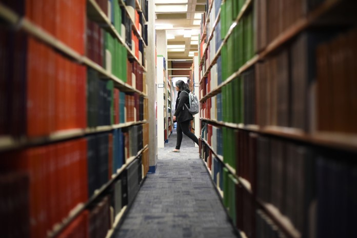 A student walks between rows of books in Homer Babbidge Library. Some students find it difficult to find time to read for fun during the semester, but others find the time to read books they love. (Zhelun Lang/Daily Campus)