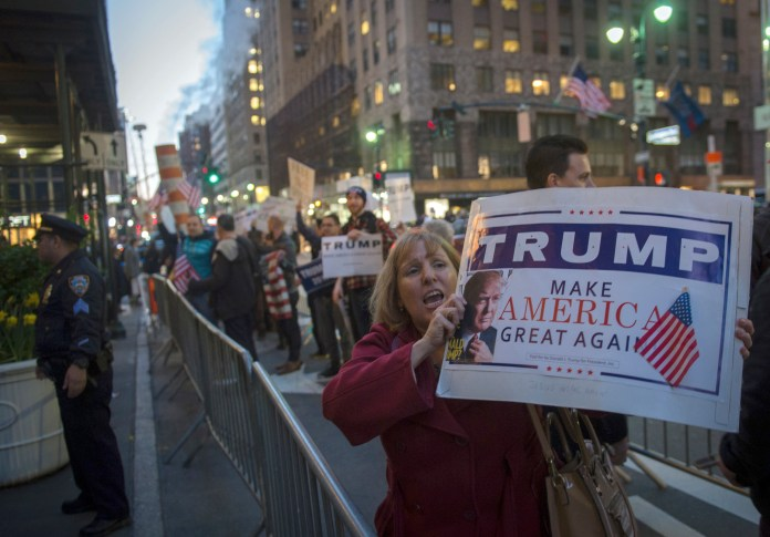A supporter of Republican presidential candidate Donald Trump holds a sign outside the New York State GOP Gala, Thursday, April 14, 2016, in New York. (AP Photo/Bryan R. Smith)