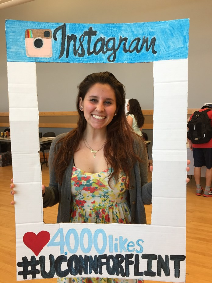 Yael Holzmen Castellands, a sixth-semester political science and communications major, poses in a cutout frame she made to raise awareness and support for donating to the people of Flint, Michigan. (Diler Haji/The Daily Campus)
