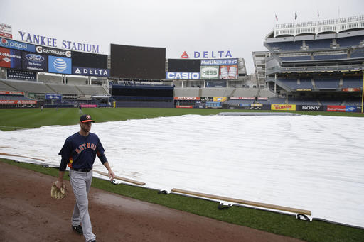 Houston Astros pitcher Doug Fister walks off a covered field in the rain at Yankee Stadium, Monday, April 4, 2016 in New York. (AP Photo/Seth Wenig)