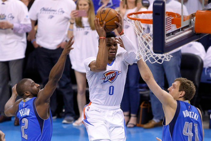 Oklahoma City Thunder guard Russell Westbrook (0) goes to the basket between Dallas Mavericks guard Raymond Felton (2) and Dallas Mavericks forward Dirk Nowitzki (41) during the first half of Game 2 of a first-round NBA basketball playoff series, Monday, April 18, 2016, in Oklahoma City. (AP Photo/Alonzo Adams)