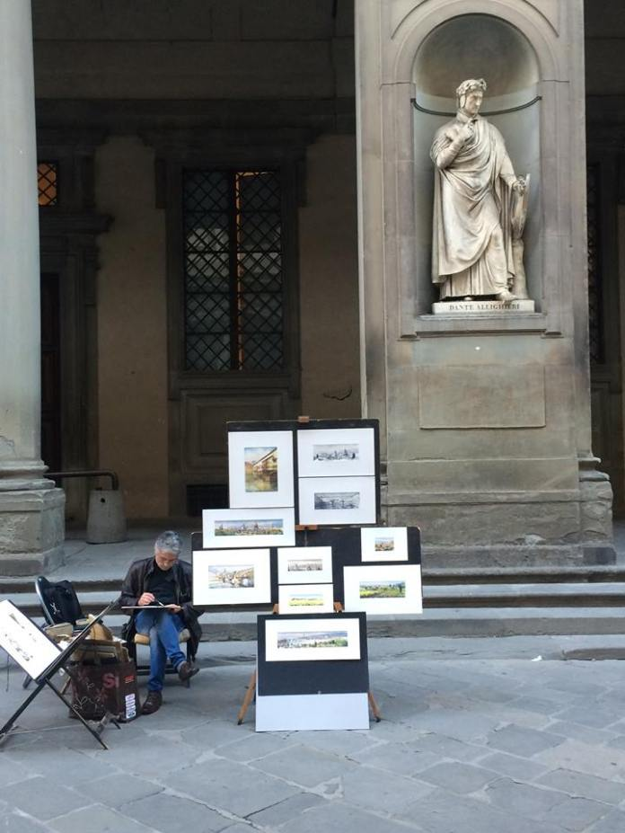 An artist paints curbside in Florence. (Sten Spinella/The Daily Campus)
