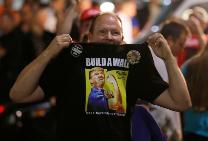 """A supporter of Republican presidential candidate Donald Trump holds up his shirt, which bears the Trump slogan """"Build a Wall,"""" following a rally for Trump, Tuesday, Aug. 30, 2016, in Everett, Wash. (Ted S. Warren/AP)"""