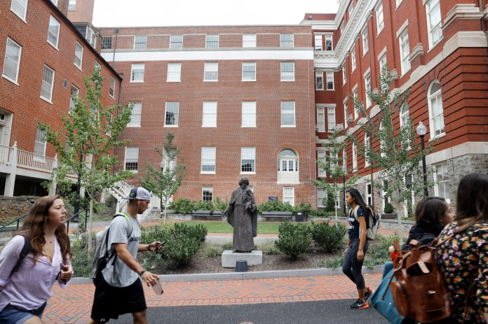 Students walk past a Jesuit statue in front of Freedom Hall, center, formerly named Mulledy Hall, on the Georgetown University campus, Thursday, Sept. 1, 2016, in Washington. After renaming the Mulledy and McSherry buildings at Georgetown University temporarily to Freedom Hall and Remembrance Hall, Georgetown University will give preference in admissions to the descendants of slaves owned by the Maryland Jesuits as part of its effort to atone for profiting from the sale of enslaved people. (Jacquelyn Martin/AP)