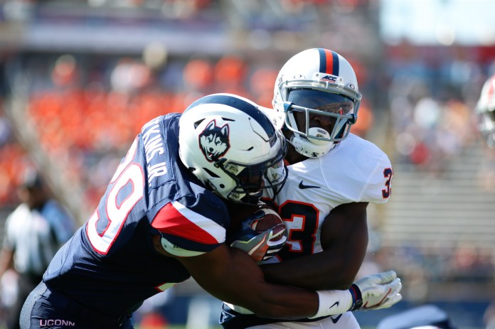 UConn safety Anthony Watkins tackles a member of the Cavalier's offensive line during UConn's 13-10 victory over UVA on September 17, 2016. (Tyler Benton/The Daily Campus)