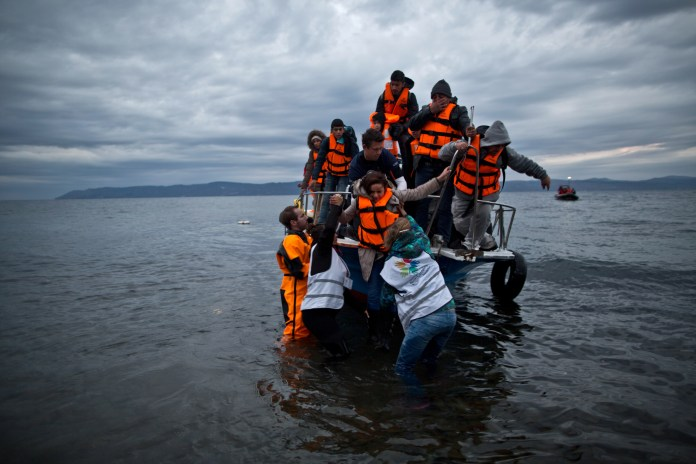 In this Thursday, Dec. 3, 2015 photo, volunteers help refugees disembark from a vessel carrying Yazidi refugee Samir Qasu, 45, from Sinjar, Iraq, and his wife Bessi, 42, their two daughters Delphine, 18, seen center left, Dunia 13, and their two sons Dilshad, 17, seen center left, and Dildar, 10, as it arrives to the northeastern Greek island of Lesbos from the Turkish coast. (Muhammed Muheisen/AP)