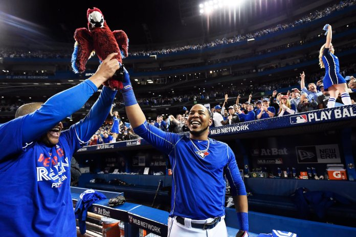 Toronto Blue Jays' Edwin Encarnacion celebrates his game winning walk-off three-run home run against the Baltimore Orioles with teammate Ezequiel Carrera during the 11th inning of an American League wild-card baseball game in Toronto, Tuesday, Oct. 4, 2016. (Nathan Denette/The Canadian Press via AP)