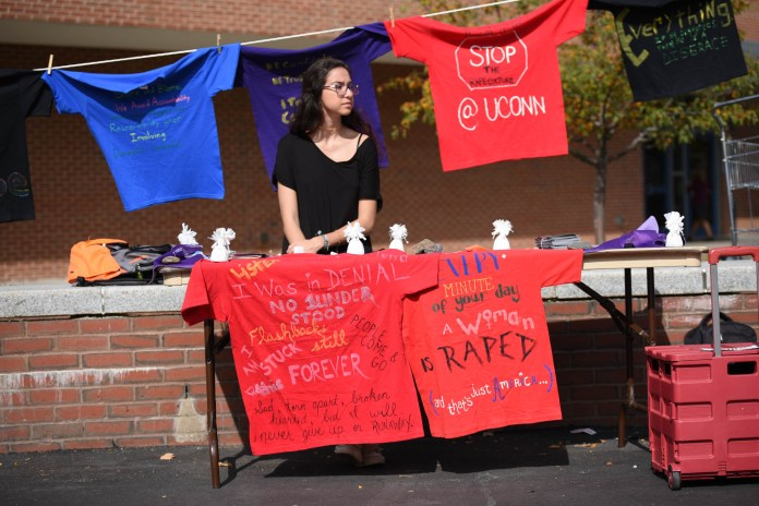 Manu Bayraktar, a junior geoscience major, volunteers for the annual Clothesline Project outside of the Student Union on Thursday, Oct. 13, 2016.Each t-shirt symbolizes the past and present experiences of a UConn student who has either suffered from sexual assault or been moved by survivors. (Zhelun Lang/The Daily Campus)