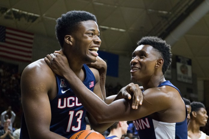 Sophomore forward Steve Enoch (13) and freshman guard Christian Vital (right) share a smile during First Night on Friday, Oct. 14 at Gampel Pavilion. Vital amassed nine points in the scrimmage, while Enoch scored eight. (Jackson Haigis/The Daily Campus)
