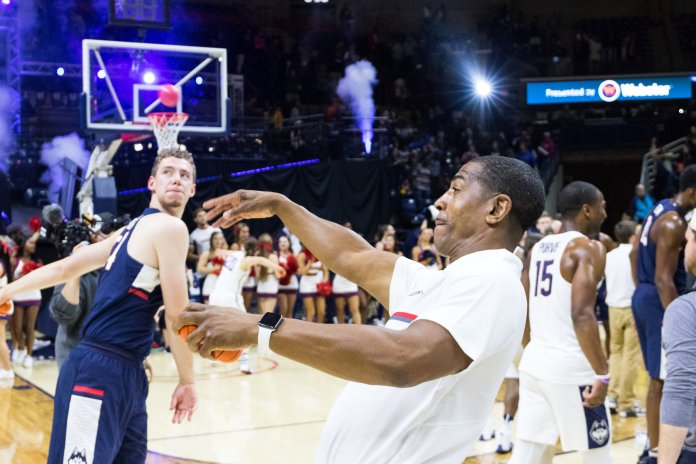 Kevin Ollie and junior forward Christian Foxen tossing fans mini basketballs after the scrimmage.