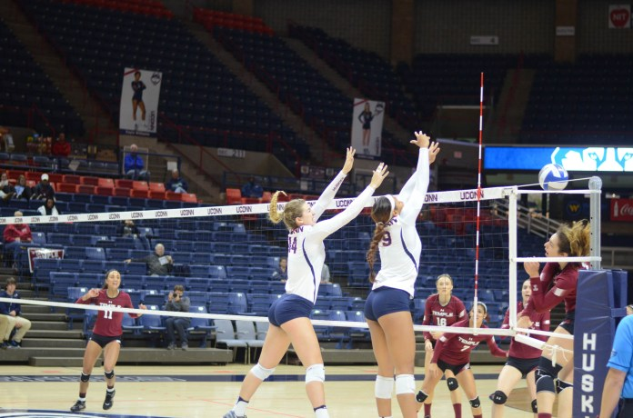 Middle blocker Hayley Cmajdalka (14) and outside hitter Camille Evans (9) attempt to block a shot during the team's 3-2 loss to Temple University on Wednesday, Sept. 28, 2016 in Gampel Pavilion. The Huskies will look for revenge as they take on the Owls Wednesday, Oct. 25 at Temple University. (Sam Mahmud/The Daily Campus)