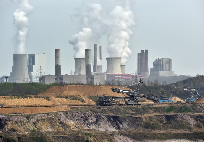 In this April 3, 2014 file photo giant machines dig for brown coal at the open-cast mining Garzweiler in front of a smoking power plant near the city of Grevenbroich in western Germany.(Martin Meissner/AP)