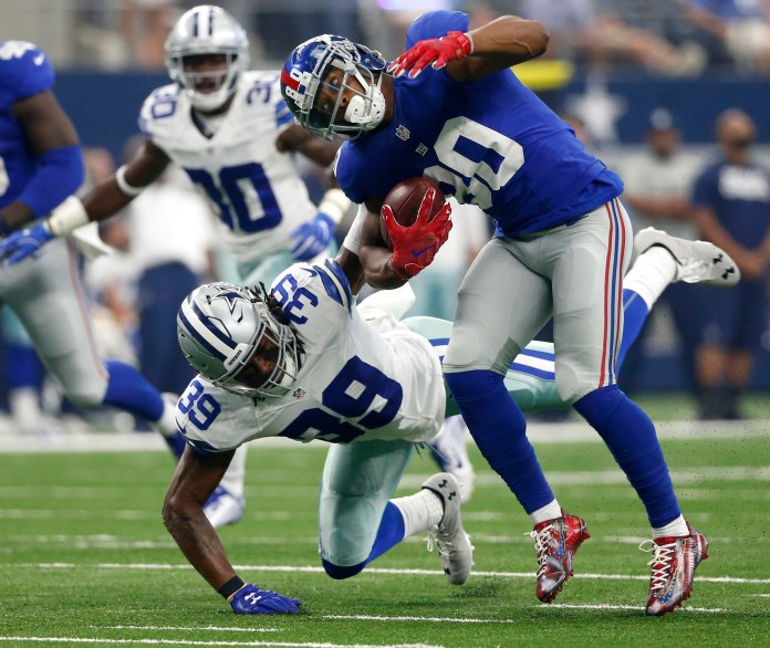 In this Sunday, Sept. 11, 2016, photo, New York Giants wide receiver Victor Cruz (80) is tackled by Dallas Cowboys cornerback Brandon Carr (39) after catching a pass during an NFL football game in Arlington, Texas. The Cowboys haven't forced a turnover in four games and couldn't get a sack of Washington's Kirk Cousins despite 53 pass attempts. After an early season surge into the top 10, the Cowboys have slid a bit. (AP Photo/Michael Ainsworth)