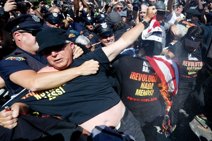 """A law enforcement officer takes Gregory """"Joey"""" Johnson into custody after he started to burn an American flag in Cleveland, during the third day of the Republican convention. President-elect Donald Trump said Tuesday that anyone who burns an American flag should face unspecified """"consequences,"""" such as jail or a loss of citizenship _ a move that was ruled out by the Supreme Court nearly three decades ago. (John Minchillo/AP)"""
