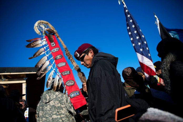 Native American veterans join an interfaith ceremony at the Oceti Sakowin camp where people have gathered to protest the Dakota Access oil pipeline in Cannon Ball, N.D., Sunday, Dec. 4, 2016. Tribal elders have asked the military veterans joining the large Dakota Access pipeline protest encampment not to have confrontations with law enforcement officials, an organizer with Veterans Stand for Standing Rock said Sunday, adding the group is there to help out those who've dug in against the four-state, $3.8 billion project. (AP Photo/David Goldman)