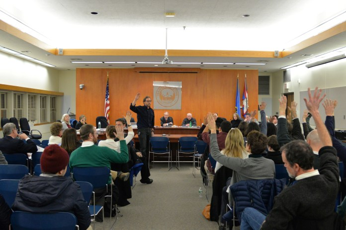 Member of the Mansfield community raise their hands to show their support for an ordinance by Mansfield to make the community a sanctuary city on Nov. 28, 2016 at Town Hall. Debate continued at a meeting on Monday, Dec. 11, 2016 but no definite decision was reached. (Amar Batra/The Daily Campus)