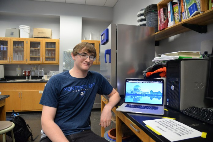 Spencer Matonis, 4 semester Material Science Engineering major, poses in his lab with his creation the Coalesce database. The database allows students to track open research labs across UConn and other universities. (Amar Batra/The Daily Campus)