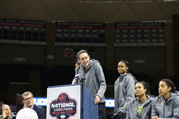 Breanna Stewart addresses the crowd at Gampel Pavilion following her fourth national championship. Coach Geno Auriemma (left) watches. The two recently came out and spoke in reaction to Candice Parker's comments on the WNBA. (Jackson Haigis/The Daily Campus)