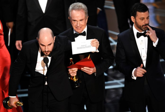 """Jordan Horowitz shows the envelope revealing """"Moonlight"""" as the true winner of best picture at the Oscars on Sunday, Feb. 26, 2017, at the Dolby Theatre in Los Angeles. Host Jimmy Kimmel and presenter Warren Beatty look on from right. (Photo by Chris Pizzello/Invision/AP)"""