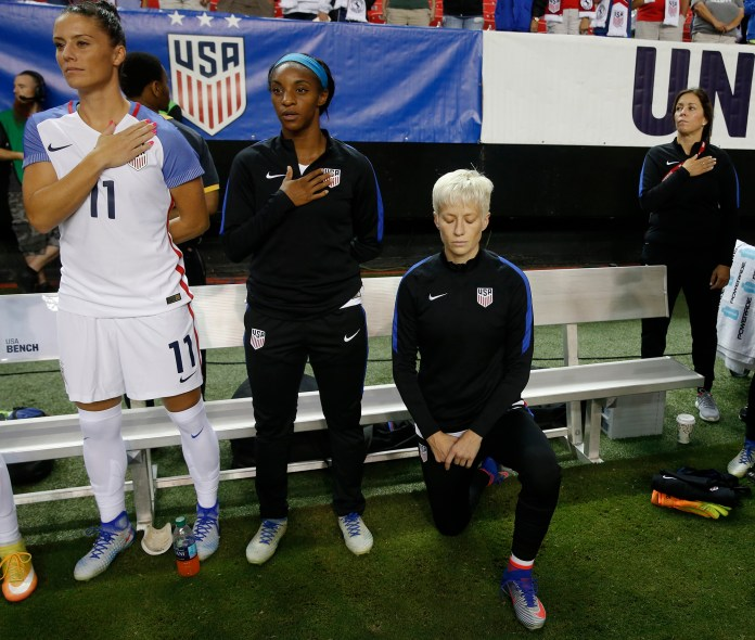 In this Sunday, Sept. 18, 2016, file photo, USA's Megan Rapinoe, right, kneels next to teammates Ali Krieger (11) and Crystal Dunn (16) as the U.S. national anthem is played before an exhibition soccer match against Netherlands, in Atlanta.(John Bazemore/AP)