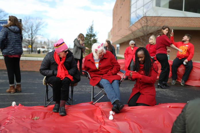 Women of the UConn community wear red and wave inspirational signs to show their support for National Women's Day on Wednesday, March 8, 2017 in Storrs, CT. (Owen Bonaventura/The Daily Campus)
