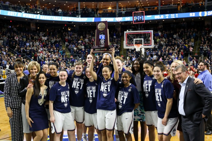 The Huskies pose for a photo with the Bridgeport Region trophy, held by senior Saniya Chong.